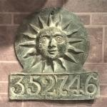 metal plaque with embossed sun and number 352746