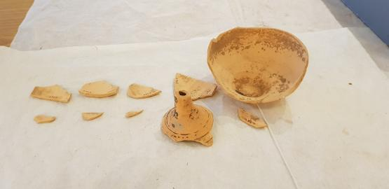 sherds of a fusiform bottle made of ceramic sit on white paper
