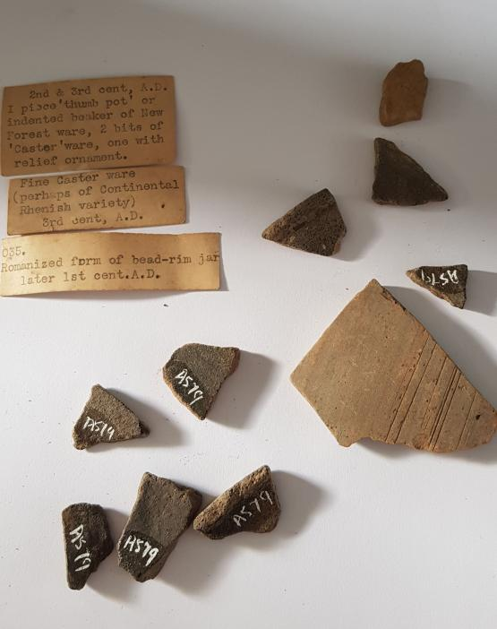a variety of broken romano british pot sherds, along with faded paper labels written on a typewriter. They are arranged on a white background.