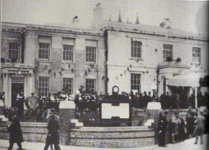 A black and white photograph showing the opening of the Manor House as Council Offices in the 1930s. The building is surrounded by people and covered in bunting.